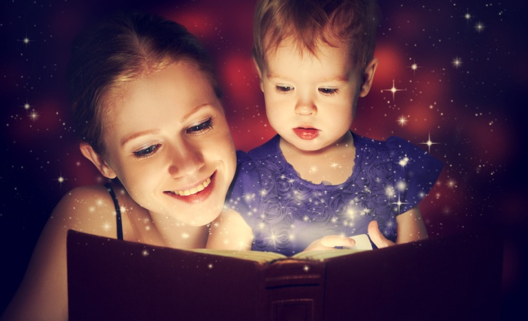 family mother and child baby daughter reading magic book in the dark